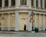 A pedestrian passes a boarded up store in the SoHo neighborhood of New York on April 11.