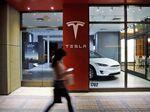 A pedestrian walks past a closed Tesla Inc. store.