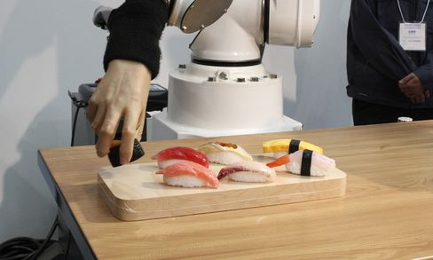 A visitor looks at a robot placing a set of waxwork sushi on a plate during a demonstration at the International Food Machinery and Technology Exhibition in Tokyo, on June 9, 2009.