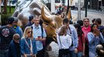 Tourists visit the Charging Bull sculpture near the New York Stock Exchange (NYSE) in New York.