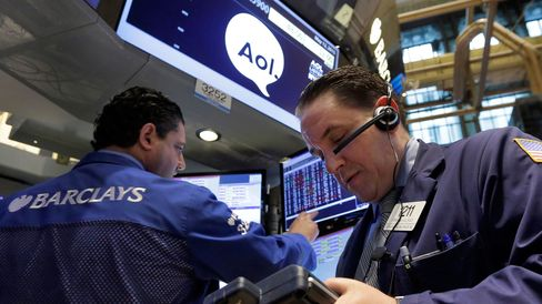 Specialist work at the post that handles AOL on the floor of the New York Stock Exchange on May 12, 2015.
