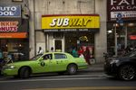 A taxi pulls out of a parking spot in front of a Subway in the Brooklyn.