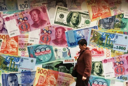 A combo of Chinese currency RMB or Yuan, US Dollar, Hong Kong Dollar and other currencies notes is seen outside a foreign exchange shop in Hong Kong on March 12, 2015.