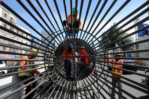 Construction workers prepare to put up a column for an elevated highway project in Manila.