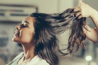 Cropped Image Of Hairdresser Holding Customer Hair In Salon