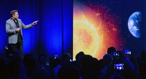 Telsa CEO Elon Musk points at the sun.