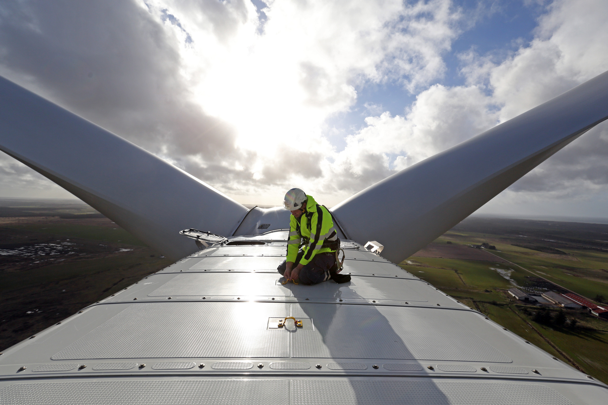 An employee checks a cable on the nacelle of a wind turbine during operational testing in Osterild, Denmark.