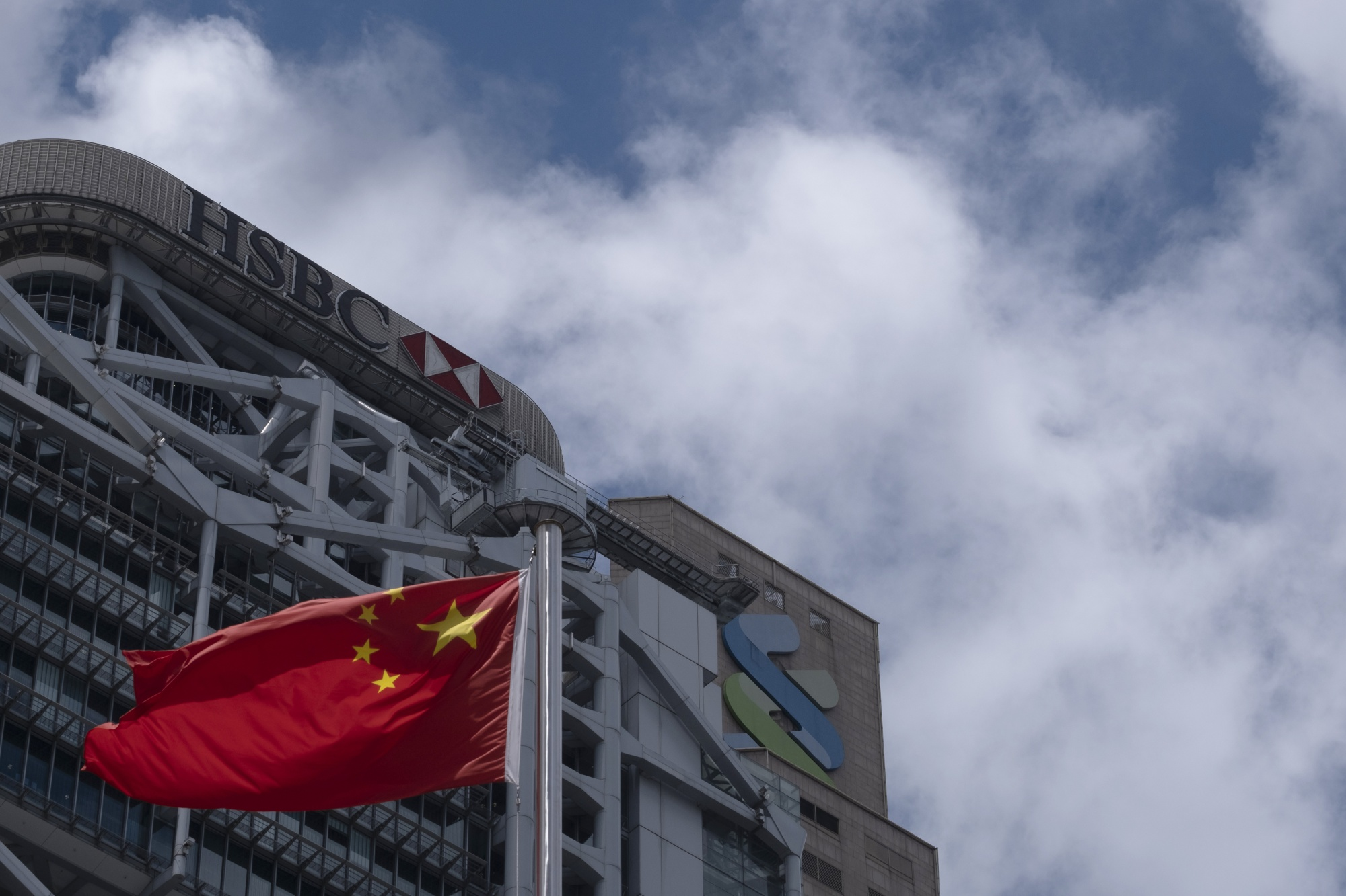 The flag of China flies near the HSBC Holdings Plc building, left, in Hong Kong.