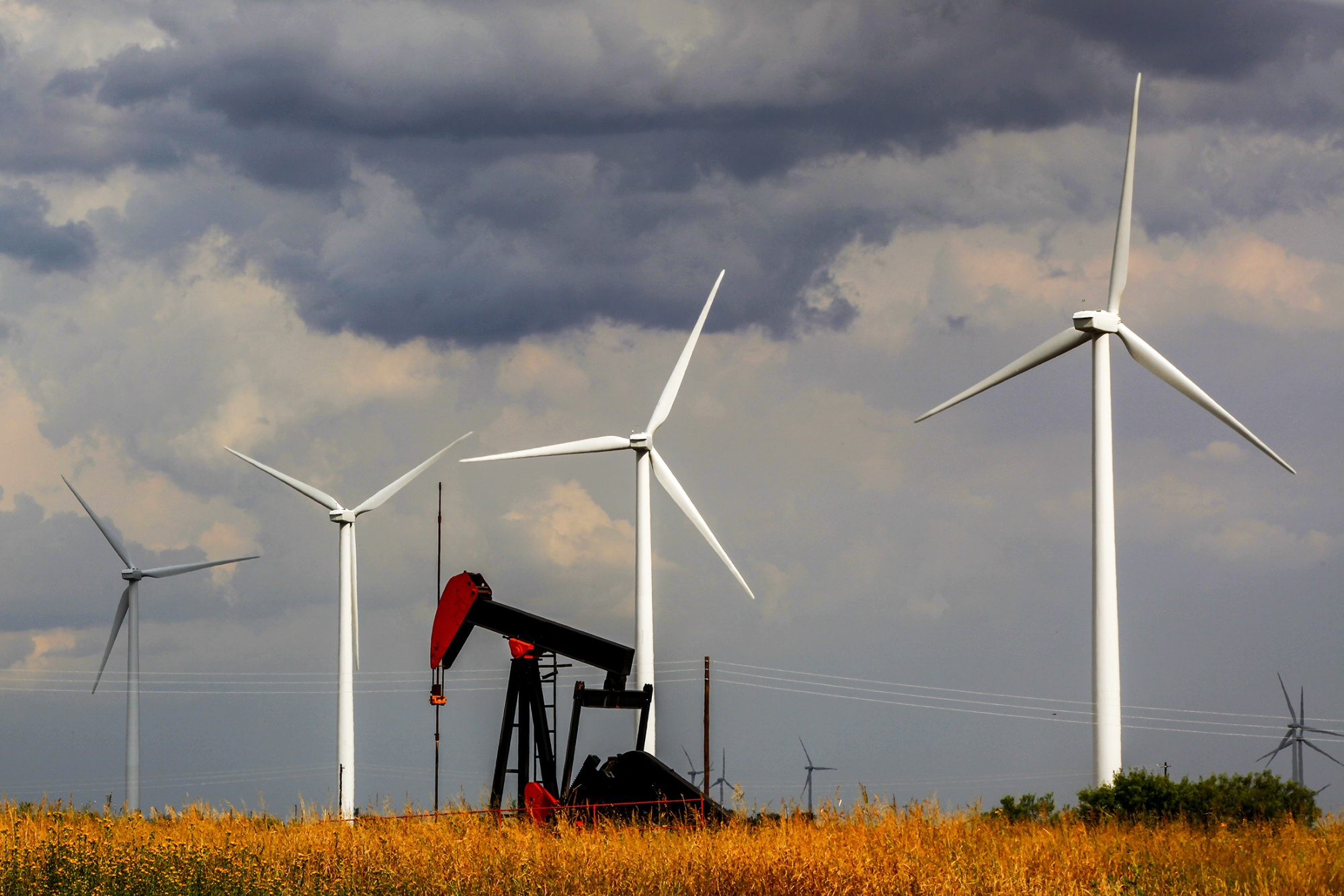 A pumpjack in front of wind turbines in West Texas.