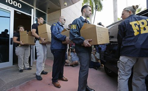 FBI agents carry boxes from the headquarters of CONCACAF in Miami Beach, on May 27, 2015.