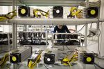 An employee checks power supply units and cooling fans linked to cryptocurrency mining machines at the SberBit mining 'hotel' in Moscow, Russia.