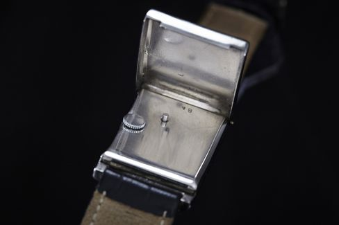 The unusual crown and winding mechanism are hidden under a hinged caseback.