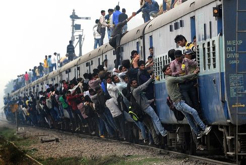 ニューデリー郊外で列車に登ったり、つかまったりする乗客