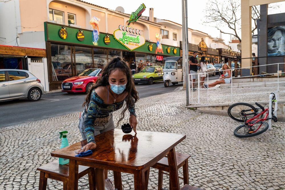 Kelnerka sprząta stół przed barem na ulicy Oura w Albufeirze w Portugalii, 29 maja.