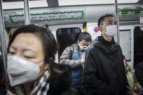 Commuters wear face masks while riding in the subway in Beijing.