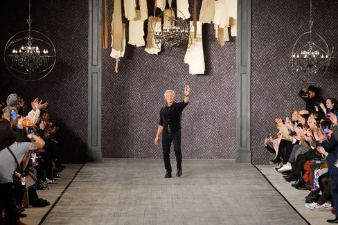 Designer Abboud waves to guests after showing his first runway collection in 15 years.