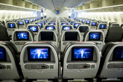 Screens are illuminated in the economy-class cabin on board an American Airlines Group Inc. Boeing Co. 777-300ER aircraft at Hong Kong International Airport in Hong Kong, China, on Friday, June 13, 2014.