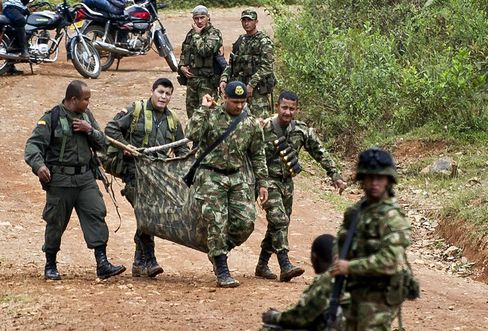 Colombian soldiers carry equipment of one of ten soldiers killed by the Revolutionary Armed Forces of Colombia (FARC) guerrillas, in the rural area of Buenos Aires, department of Cauca, Colombia.
