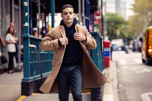 """New York is the perfect backdrop to depict loneliness. There's a certain feel about Elliot in the hoodie walking around this city that you just couldn't get anywhere else."" On Malek: Massimo Alba cashmere hoodie, $840; Jil Sander camel overcoat, $2,935; J Brand Tyler slim-fit jeans, $228; Hamilton Jazzmaster GMT, $1,495."