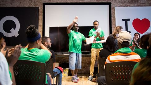 Anthony Knox, center, isgiven an award during a Managed by Q team meeting.