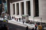 Pedestrians walk along Wall Street near the New York Stock Exchange.