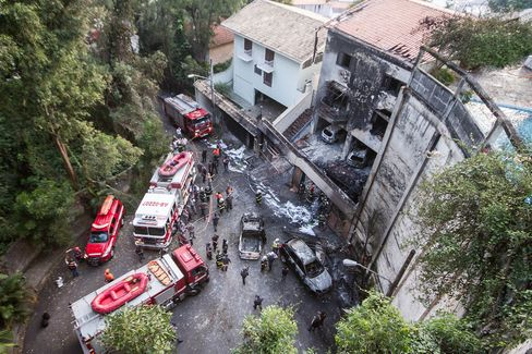 Firefighters at the scene of the wreckage where a small plane crashed into a house in Sao Paulo, Brazil on March 19.
