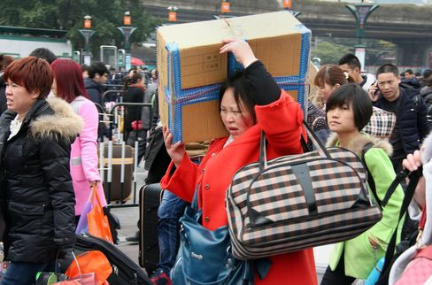 Travellers arrive with their bags at one of the main train stations in Guangzhou as they prepare to head home for the upcoming Lunar New Year.