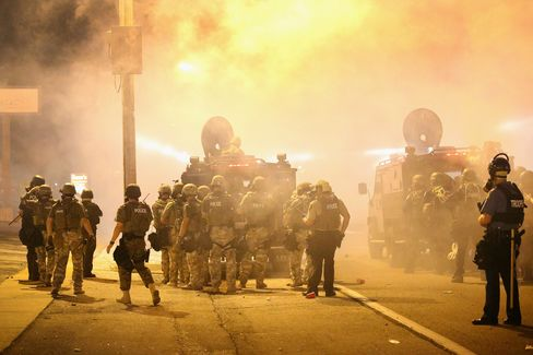 Police advance through a cloud of tear gas toward demonstrators protesting the killing of teenager Michael Brown in Ferguson. Much of the equipment used in Ferguson came from a U.S. Defense Department program that provides used gear to local police departments for counterterrorism. Photographer: Scott Olson/Getty Images
