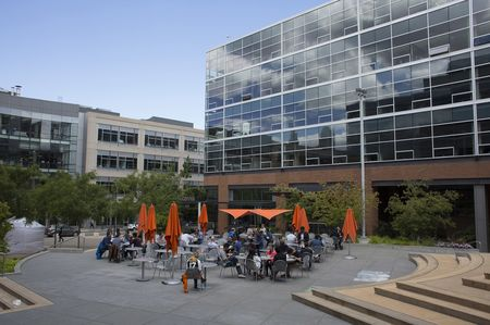 People eat lunch in a courtyard outside the Amazon offices.