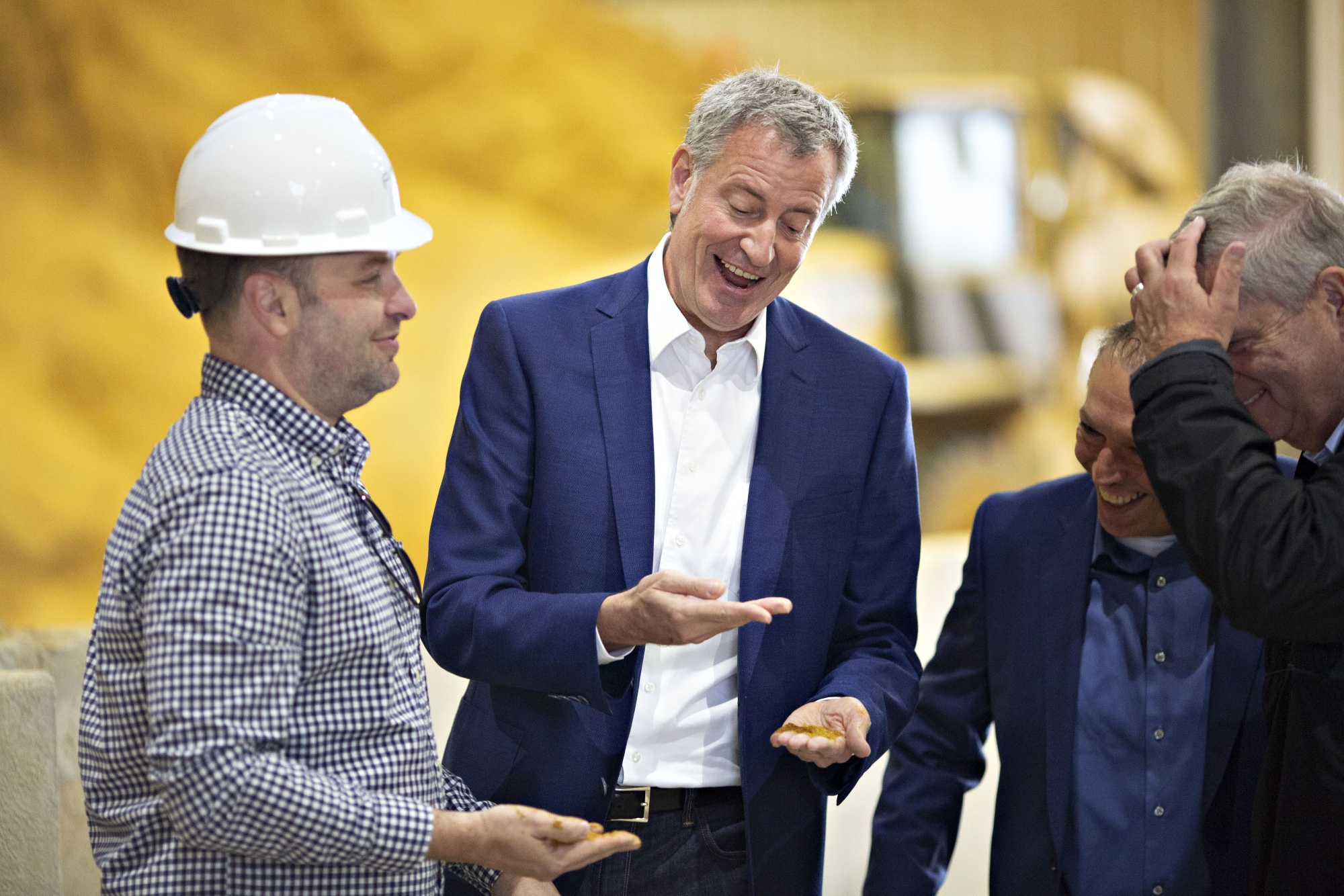 Bill de Blasio, center, smiles while holding a handful of dried distillers grains in Iowa.
