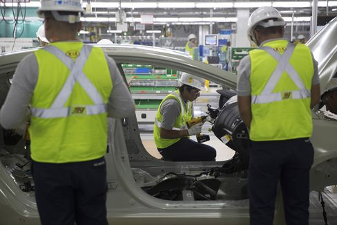 Workers check the chassis of a vehicle during a test at the Kia Motors assembly plant.