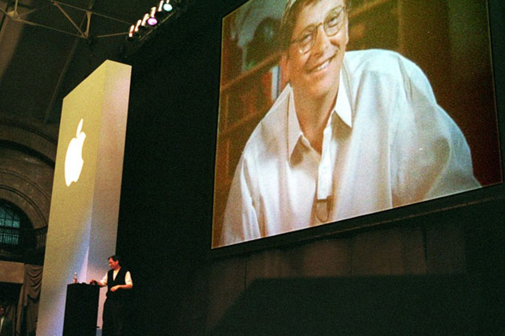 Steve Jobs stands at a podium as Bill Gates appears on a video screen as he addresses the MacWorld convention praising the new alliance between Apple and Microsoft on Aug. 6, 1997 in Boston