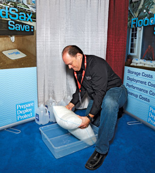 "Eckstein demonstrates the FloodSax, a ""sandless sandbag"" that expands from the size of a doormat to a 44-pound, 18-by-21-inch block by absorbing 5 gallons of water"