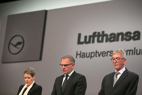 Simone Menne, chief financial officer of Deutsche Lufthansa AG, left, Carsten Spohr, chief executive officer of Deutsche Lufthansa AG, center, and Wolfgang Mayrhuber, chairman of Deutsche Lufthansa AG, observe a minute's silence for the victims of last month's Germanwings aircrash during the airline's AGM in Hamburg on April 29, 2015.