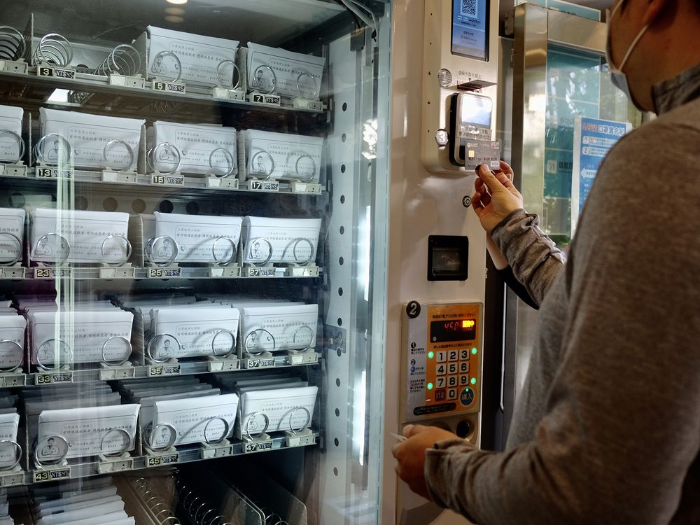 A resident buys face masks from a vending machine in Taipei on April 14.