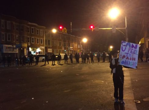 A girl poses with a sign in front of a line of police near the scene where riots broke out in Baltimore on Monday.