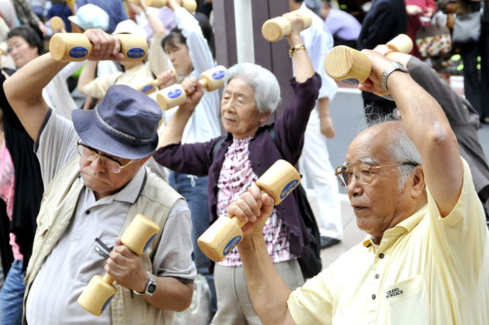 Elderly people work out with wooden dumbbells in Tokyo