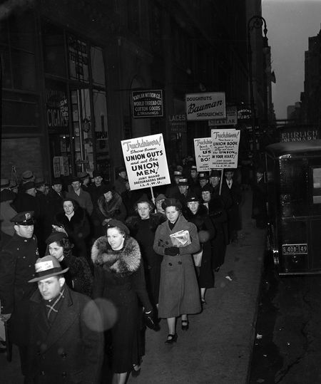 """Members of the International Ladies' Garment Workers Union and the Dressmakers' Union picket in front of dressmakers' businesses in the Garment District, hoping union truck drivers will honor their picket line and not make deliveries, on March 10, 1938. Their signs read: """"Truck drivers! Show your union guts and act like union men!"""""""
