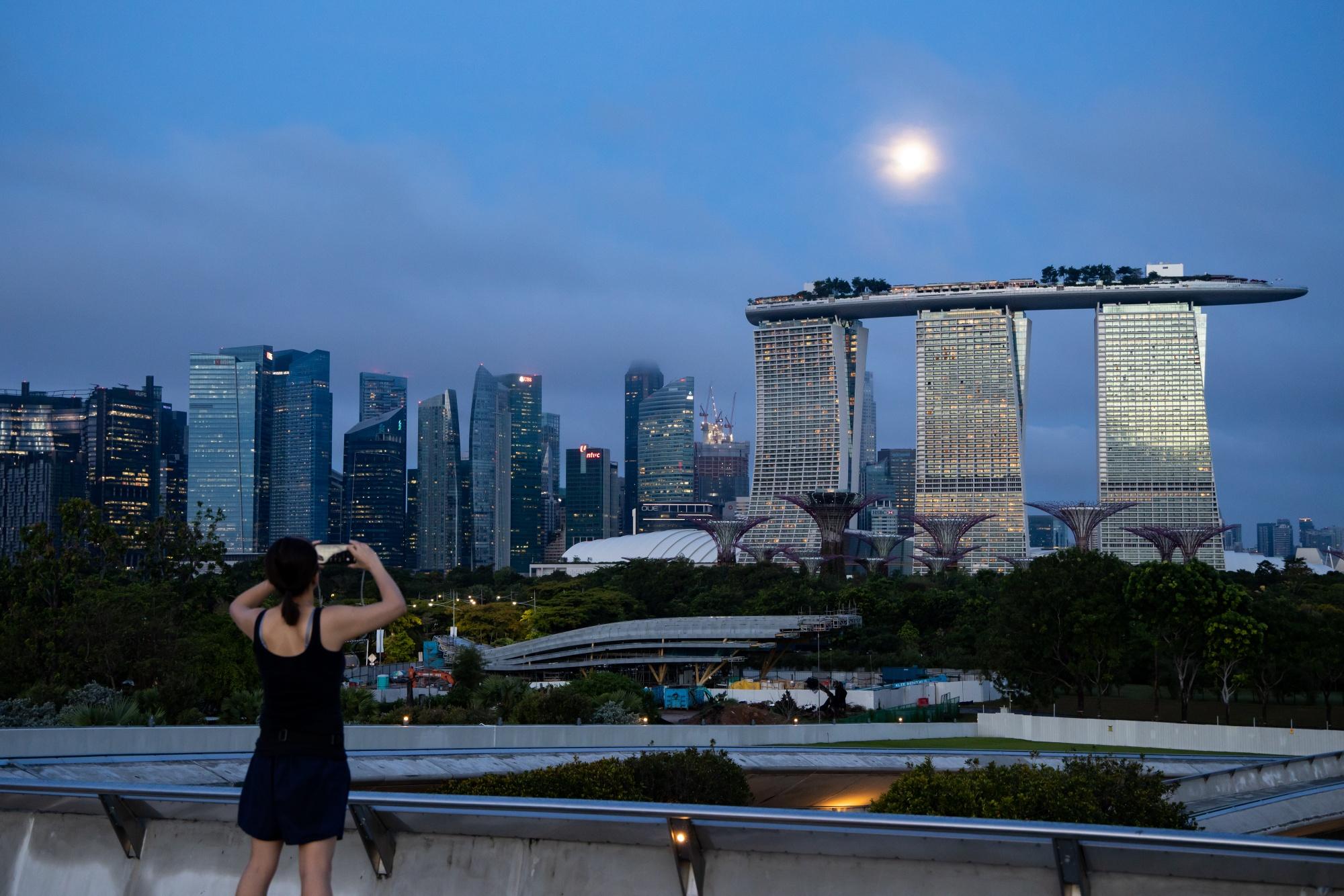 Seseorang dengan smartphone mengambil foto hotel dan kasino Marina Bay Sands.