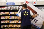 An employee moves a TCL Corp. television in shopping cart at a Wal-Mart Stores Inc. location in Burbank, California, U.S.