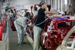 Employee carry out final inspections on the body shells of freshly painted Nissan Micra, right, and Renault Clio, second left, automobiles inside the Renault SA factory in Flins, Franc.