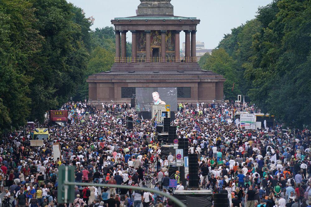 Ludzie zbierają się pod Kolumną Zwycięstwa w centrum miasta, aby wysłuchać przemówień podczas protestu przeciwko ograniczeniom związanym z koronawirusem i polityce rządu 29 sierpnia.