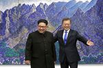 Moon Jae-in, South Korea's president, right, gestures, as he stands with Kim Jong Un, North Korea's leader.