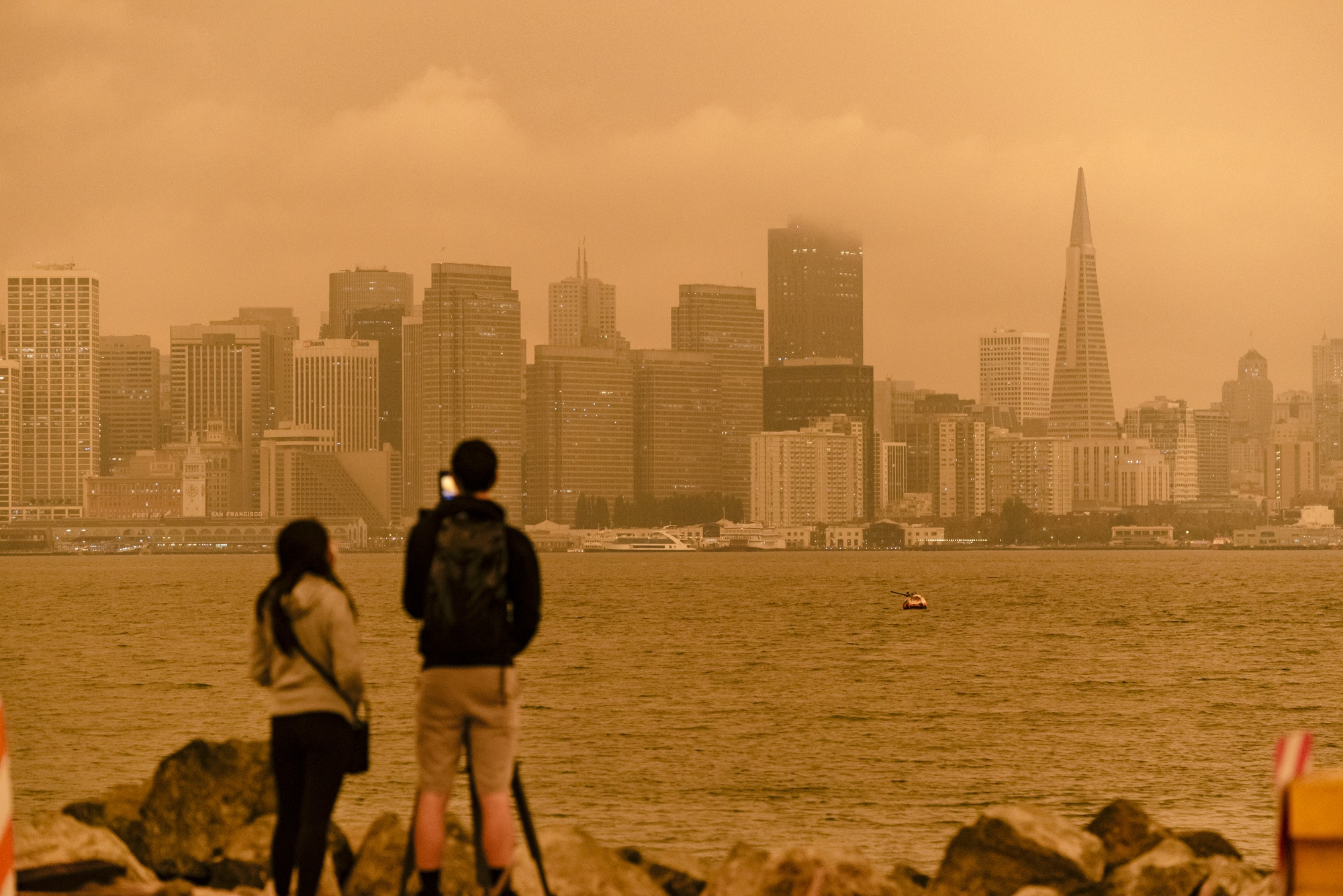 People take pictures as smoke from California wildfires hangs over the San Francisco skyline in San Francisco. A recent study found that many cities may be under-counting their carbon emissions. The problem is: There's no one right way to keep track.