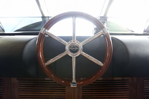 A steering wheel sits on the captain's deck aboard a 131 yacht.