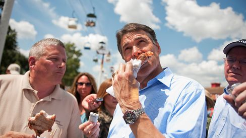 AUGUST 15, 2011: Republican presidential candidate Texas Gov. Rick Perry, right, eats a pork chop with Iowa Secretary of Agriculture Bill Northey for Secretary of Agriculture at the Iowa State Fair in Des Moines, Iowa.