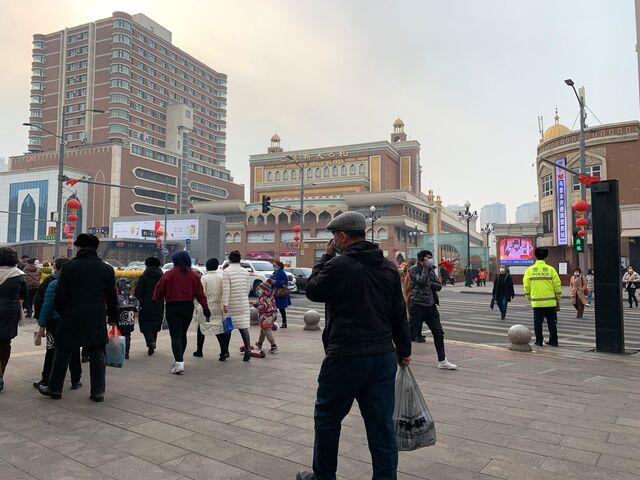 Shoppers walk past the Xinjiang International Grand Bazaar in Urumqi, capital of China's Xinjiang province.