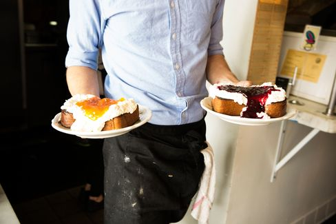 A server at Sqirl is about to make someone's day with some generously piled, overflowing-with-jam toasts.