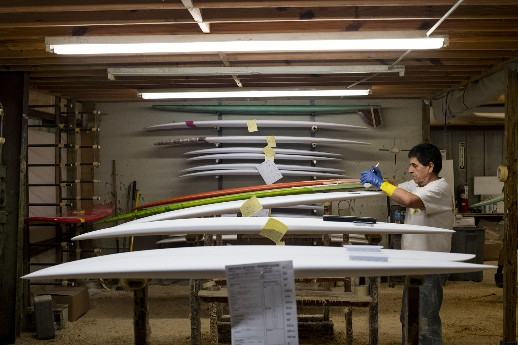 An employee laminates styrofoam shaped blanks with resins at a surboard manufacturing facility in Rockledge, Florida.