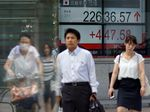 People walk past a stock indicator showing share prices on the Tokyo Stock Exchange.